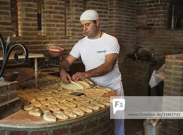 'Baker making Tonis puri  a type of Georgian bread  at the Bread House Georgian Restaurant; Tbilisi  Georgia'