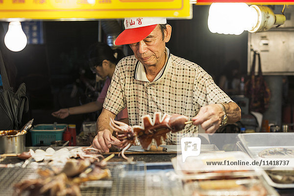 'Local night markets of Taipei are really famous because it's delicious food  a male vendor preparing his specialty food; Taiwan  China'