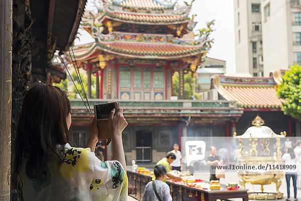 'Buddhist Longshan temple in the city center of Taipei  people praying and burning incense while a tourist take a picture; Taipei  Taiwan  China'