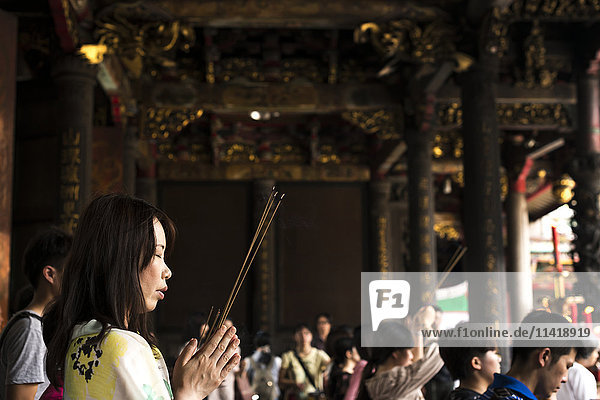 'Buddhist Longshan temple in the city center of Taipei  people praying and burning incense; Taipei  Taiwan  China'