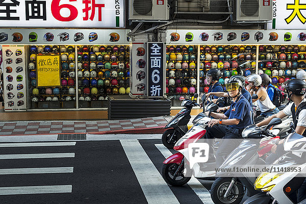 'The motorbikes and scooters in Taibei city are really a big number  helmet shop in view with scooters stopped on the road; Taiwan  China'