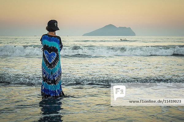 'A young woman looking out to the horizon  Waiao beach in Yilan Country  beautiful volcanic beach; Taiwan  China'
