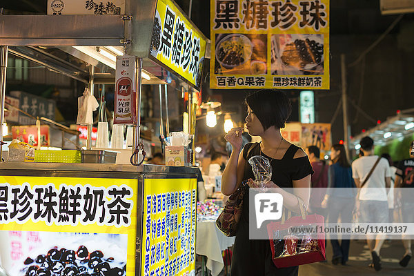'Local night markets of Taipei are really famous because it's delicious food  a youjng woman enjoying some snacks; Taipei  Taiwan  China'