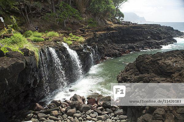 'Waterfalls into ocean cove  Queens Bath; Princeville  Kauai  Hawaii  United States of America'