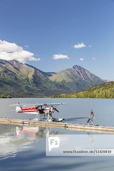 Two women disembark from a float plane docked at the Trail Lake Float Plane Base on a clear day  the Kenai Mountains in the Background  Kenai Peninsula  Southcentral Alaska  USA  Summer