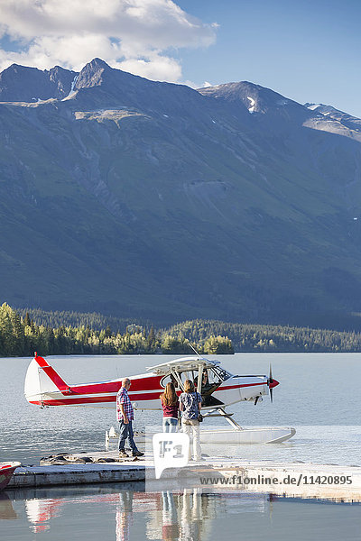 Visitors wait for the pilot to dock while  Trail Lake Float Plane Base  Moose Pass  Kenai Peninsula  Southcentral Alaska  USA