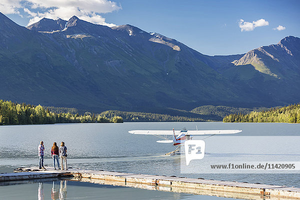 Visitors watch a float plane depart  Trail Lake Float Plane Base  Moose Pass  Kenai Peninsula  Southcentral Alaska  USA