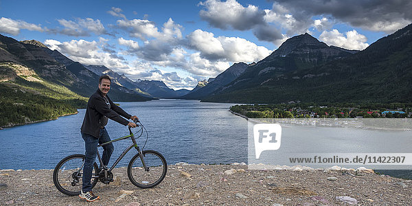 'A man sits on a bicycle at the water's edge with the Rocky mountains and a lake in the background  Waterton Lakes National Park; Alberta  Canada'