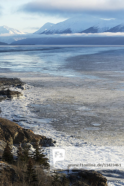 Man standing on a ledge next to the Seward Highway and Turnagain Arm  Southcentral Alaska  USA