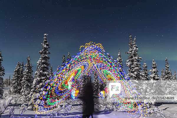 'The Aurora Borealis dances over the top of a vibrant spiral light painting  the blurry figure of a man in the middle of the light painting  moonlight casting shadows on snow covered spruce trees on a clear winter night  interior Alaska; Gakona  Alaska  United States of America'