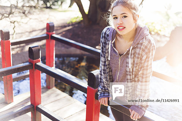 'A pretty teenage girl makes a playful pose on a boardwalk in the park with sunlight from behind; New Westminster  British Columbia  Canada'
