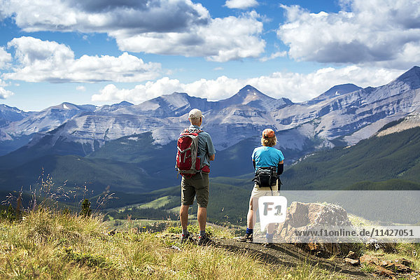 'Male and female hikers standing on top of rocky hill overlooking mountain range and valley with blue sky and clouds  West of Bragg Creek; Alberta  Canada '