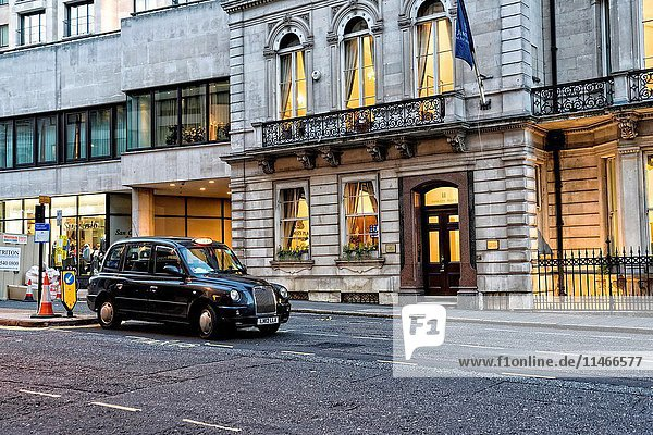 London  England  UK. Black Taxi Cab Waiting Ourside of a Residence.