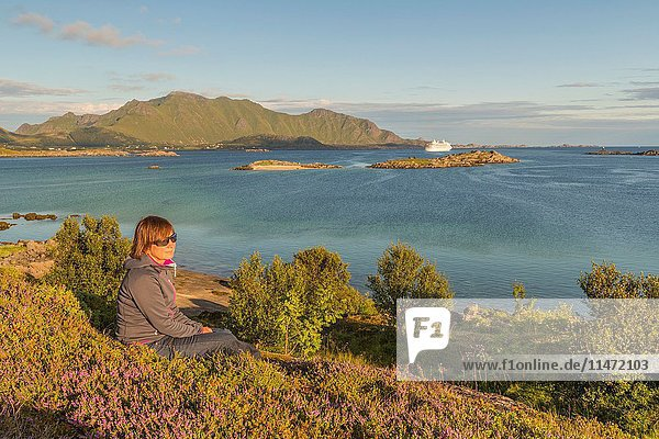 Woman sitting at the ocean in evening light  a cruise liner is going out to sea and high mountains in the background  Gravdal  Lofoten Islands  Norway.