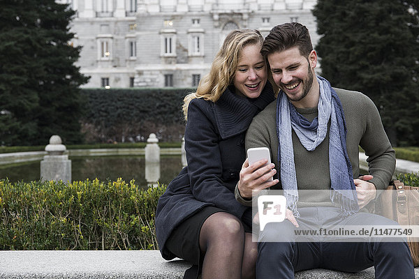 Spain  Madrid  happy couple with cell phone with the Royal Palace in background