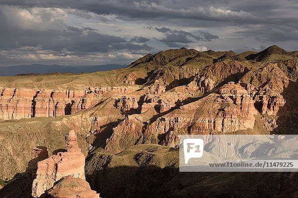 Couple taking picture at sunset on top of Hoodoo at Charyn Canyon Kazakhstan.
