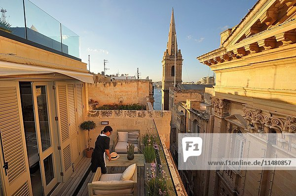 Terrace of Casa Ellul Hotel in front of the Our Lady of Mount Carmel Church and St. Paul's Anglican Pro-Cathedral  Old Theatre Street  Valletta  Malta  Southern Europe.