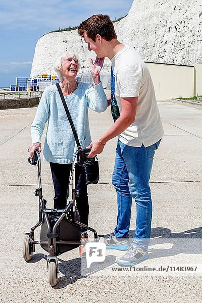 An Elderly Disabled Woman Using A Rollator Walking Aid Helped By Her Grandson  Brighton  Sussex  UK.