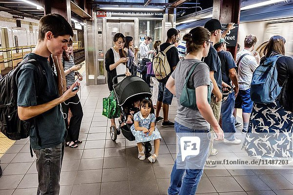 New York  New York City  NYC  Manhattan  Upper West Side  96th Street  subway  station  platform  Asian  woman  man  young adult  girl  stroller  teen  boy  student  commuters