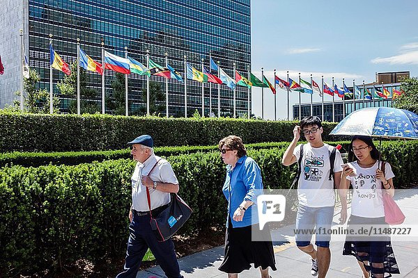New York  New York City  NYC  Manhattan  Midtown  Turtle Bay  United Nations Headquarters  exterior  flags  Asian  man  woman  senior  young adult  couple  walking