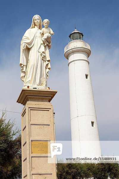 Statue of Mary holding Jesus  and the lighthouse  Punta Secca  Santa Croce Camerina  Sicily  Italy.