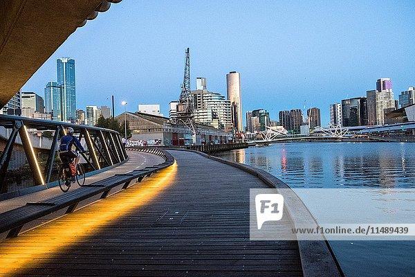 Cyclist on Jim Stynes Bridge  below Wurundjeri Way  with view of Southbank  Melbourne.