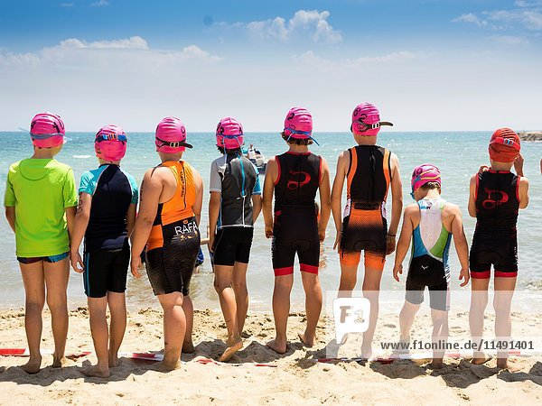 Guys ready for swimming race on the beach. in Alicante