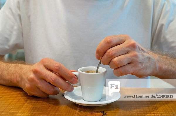Man's hands stiring a cup of coffee. Close view.