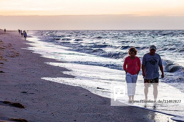 Florida  Sanibel Island  dawn  sunrise  surf  Gulf of Mexico  shellers shell hunters  beachcombers  man  woman  couple