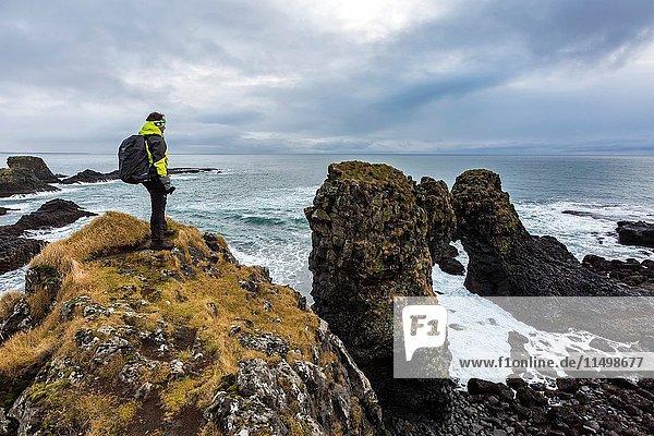 A man admires the ocean and its rocks near Arnarstapi  Snaefellsnes peninsula  Western Iceland  Europe.