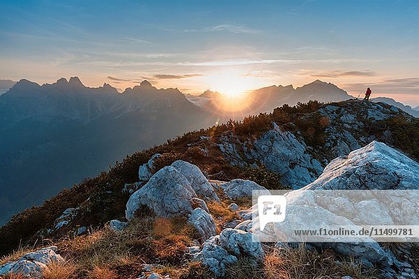 Europe  Italy  Veneto  Belluno. Hiker is looking at the rising sun fron the top of mount Celo  Dolomites  Agordino valley.