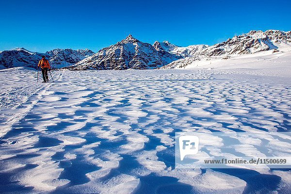 A hiker walking along a trail in the snow at the Alpe Prabello  Prabello Alp at the sunset  Valmalenco  Valtellina  Italy.