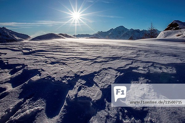 Sunburst view of Monte Disgrazia  surrounded by surreal shapes created by the winter wind  Valmalenco  Valtellina  Lombardy Italy Europe.