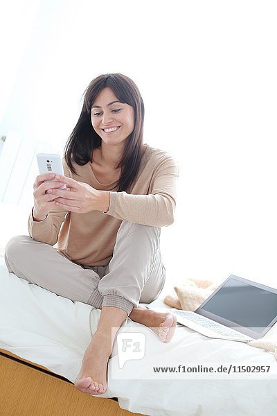 Woman using smartphone and smiling