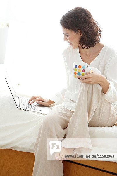 Woman using laptop computer and smiling