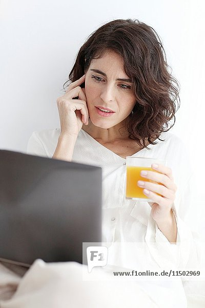 Woman using laptop computer and holding a glass of juice