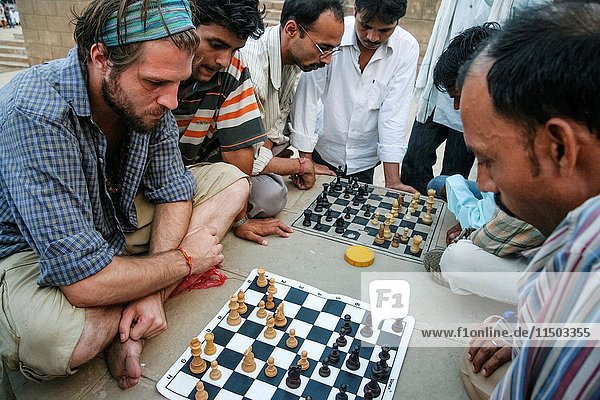 French tourist playing chess with Indian men at the street in Varanasi  Uttar Pradesh  India  Asia.