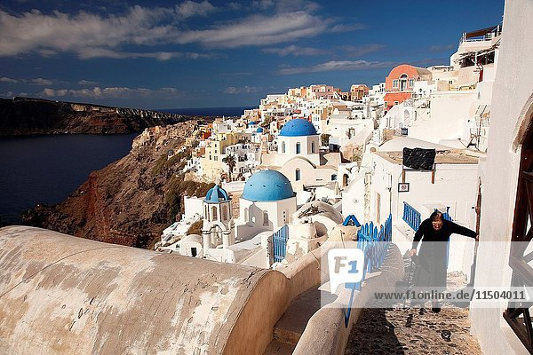 Old woman wearing black dress with stick in the alleys of Oia town with the traditional Cyclades houses of the village at the background  Santorini  Cyclades Islands  Greek Islands  Greece  Europe.