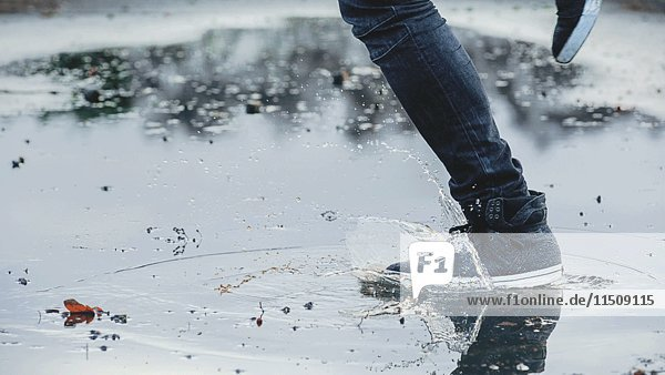 Foot with High-top Sneaker Splashing in Puddle