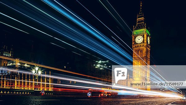 Big Ben with Streaking Bus Lights and Work Crew in Foreground at Night  London  England  UK