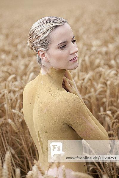 Junge Frau mit Bodypainting im Weizenfeld