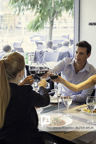 Friends clinking wine glasses in restaurant