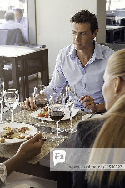 Mann beim Essen im Restaurant mit Freunden