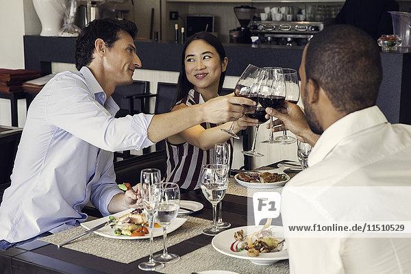 Paar klirrende Gläser in Restaurants mit Freunden