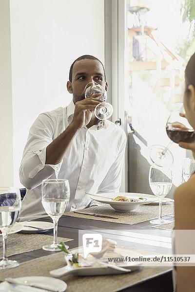 Mann trinkt Wein im Restaurant