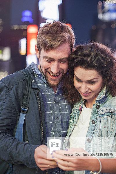 Junges Paar liest Textnachricht  die auf dem Handy empfangen wird