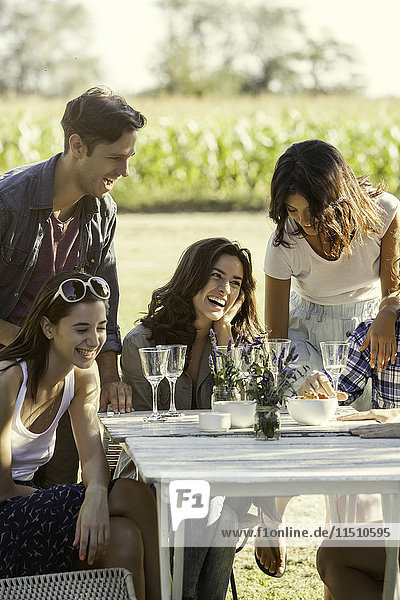 Friends laughing while enjoying meal together outdoors