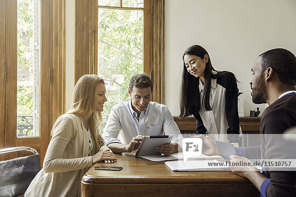 Geschäftsmann bei der Suche nach digitalen Tabletts mit Kollegen in der Sitzung
