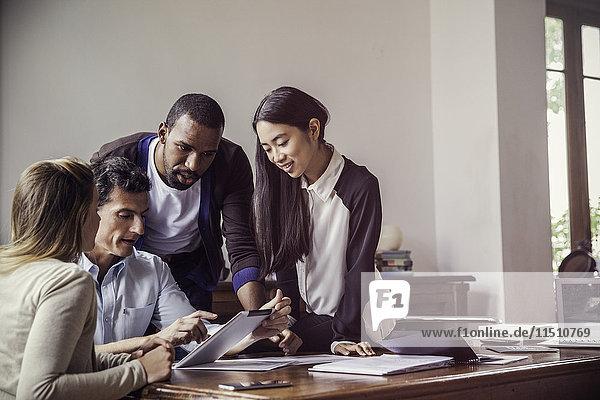 Kollegen  die gemeinsam im Büro ein digitales Tablett betrachten