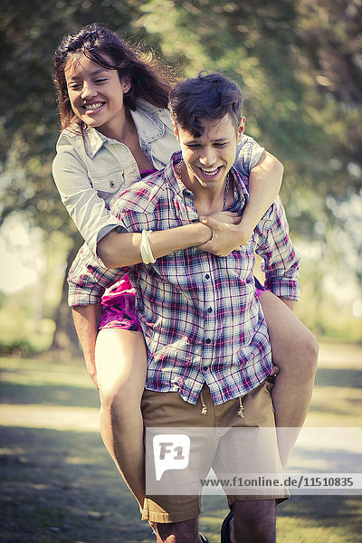 Man giving girlfriend piggyback ride in park
